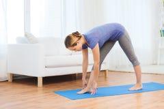 Donna che rende ad yoga posa intensa di allungamento sulla stuoia Fotografia Stock Libera da Diritti