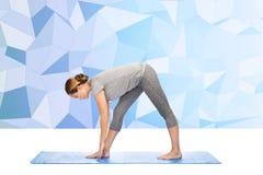 Donna che rende ad yoga posa intensa di allungamento sulla stuoia Immagine Stock Libera da Diritti