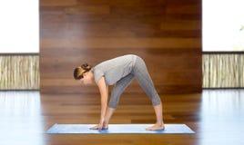 Donna che rende ad yoga posa intensa di allungamento sulla stuoia Immagini Stock Libere da Diritti