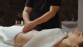 Donna che riceve massaggio dello stomaco in stazione termale, rilassantesi tramite il massaggio delle anti-celluliti archivi video