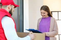 Donna che riceve pacchetto dal corriere di servizio di distribuzione fotografia stock