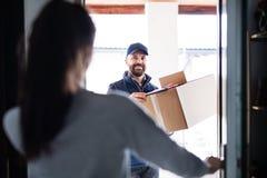Donna che riceve pacchetto dal fattorino alla porta Fotografia Stock