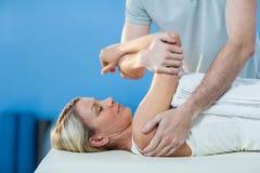 Donna che riceve terapia della spalla dal fisioterapista Immagini Stock