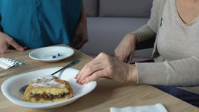 Donna che rifiuta di mangiare torta, infermiere che prova a persuadere, problema di digestione di vecchiaia stock footage