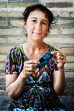 Donna che rimpicciolisce le scarpe tricottate per i bambini immagini stock libere da diritti