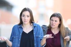 Donna che rimprovera il suo amico confuso che vi esamina fotografia stock libera da diritti