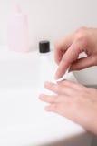 Donna che rimuove lo smalto per unghie con l'acetone Fotografia Stock