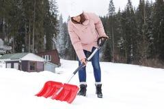 Donna che rimuove neve con la pala fotografie stock