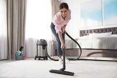 Donna che rimuove sporcizia dal tappeto con l'aspirapolvere fotografia stock