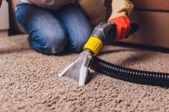 Donna che rimuove sporcizia dal tappeto con l'aspirapolvere nella sala fotografia stock