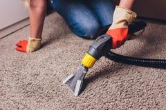 Donna che rimuove sporcizia dal tappeto con l'aspirapolvere nella sala fotografia stock libera da diritti