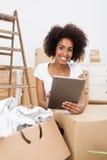 Donna che rinnova la sua casa facendo uso di un compressa-pc Immagini Stock