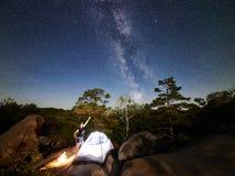 Donna che riposa accanto al campo, al falò ed alla tenda turistica alla notte fotografia stock libera da diritti