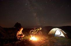 Donna che riposa alla notte che si accampa vicino al fuoco di accampamento, tenda turistica, bicicletta sotto il cielo di sera in fotografia stock