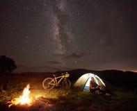Donna che riposa alla notte che si accampa vicino al fuoco di accampamento, tenda turistica, bicicletta sotto il cielo di sera in fotografie stock libere da diritti