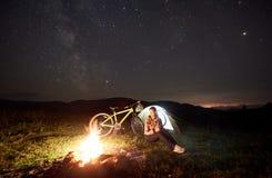 Donna che riposa alla notte che si accampa vicino al fuoco di accampamento, tenda turistica, bicicletta sotto il cielo di sera in fotografia stock libera da diritti