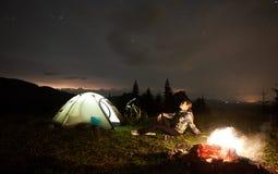 Donna che riposa alla notte che si accampa vicino al fuoco di accampamento, tenda turistica, bicicletta sotto il cielo di sera in fotografie stock