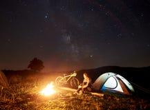 Donna che riposa alla notte che si accampa vicino al fuoco di accampamento, tenda turistica, bicicletta sotto il cielo di sera in immagini stock libere da diritti