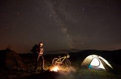 Donna che riposa alla notte che si accampa vicino al fuoco di accampamento, tenda turistica, bicicletta sotto il cielo di sera in immagini stock