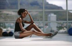 Donna che riposa dopo l'addestramento intenso allo studio di forma fisica fotografie stock libere da diritti