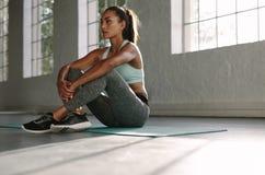 Donna che riposa dopo l'allenamento alla palestra Immagini Stock