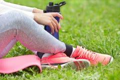 Donna che riposa dopo l'allenamento su erba Immagini Stock