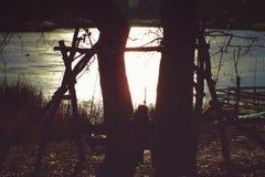 Donna che riposa su un'oscillazione vicino al lago della molla al tramonto immagini stock