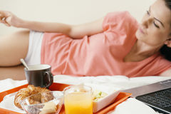 Donna che riposa sul letto e che mangia prima colazione fotografia stock