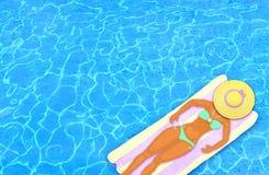 Donna che riposa sul materasso di aria di galleggiamento in uno stagno Immagini Stock Libere da Diritti