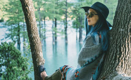 Donna che riposa sull'albero in parco Fotografie Stock