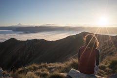 Donna che riposa sulla cima della montagna Immagini Stock