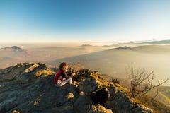 Donna che riposa sulla cima della montagna Immagine Stock