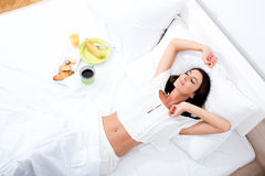 Donna che risiede nel letto con la prima colazione Fotografie Stock