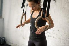 Donna che risolve con gli anelli relativi alla ginnastica alla palestra adatta dell'incrocio Fotografia Stock Libera da Diritti