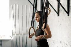 Donna che risolve con gli anelli relativi alla ginnastica alla palestra adatta dell'incrocio Immagini Stock Libere da Diritti