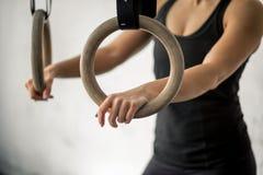 Donna che risolve con gli anelli relativi alla ginnastica alla palestra adatta dell'incrocio Fotografie Stock