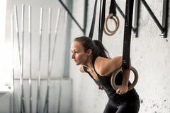 Donna che risolve con gli anelli relativi alla ginnastica alla palestra adatta dell'incrocio Fotografie Stock Libere da Diritti