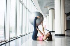 Donna che risolve con la palla di esercizio in palestra Donna di Pilates che fa gli esercizi nella stanza di allenamento della pa Immagini Stock Libere da Diritti