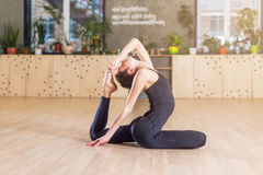 Donna che risolve nello studio che fa allungando esercizio che si siede nella posizione zoppicanta di re Pigeon di yoga Fotografie Stock Libere da Diritti