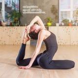Donna che risolve nello studio che fa allungando esercizio che si siede nella posizione zoppicanta di re Pigeon di yoga Fotografia Stock Libera da Diritti