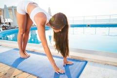 Donna che risolve sulla stuoia di yoga all'aperto Fotografia Stock