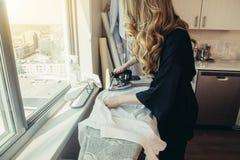 Donna che riveste di ferro con il ferro professionale con il vapore di acqua a casa fotografie stock libere da diritti