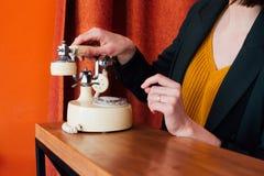Donna che rivolge ad un retro telefono Immagine Stock