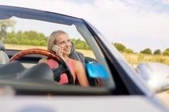 Donna che rivolge allo smartphone all'automobile convertibile Fotografia Stock Libera da Diritti