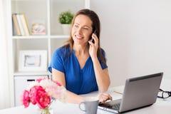 Donna che rivolge allo smartphone a ufficio o casa Immagine Stock Libera da Diritti