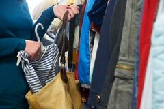 Donna che ruba i vestiti dal deposito Immagini Stock