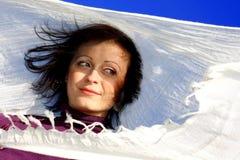 Donna che salta nel vento con una sciarpa immagine stock