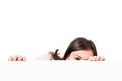 Donna che sbircia sopra il fondo bianco. Fotografie Stock
