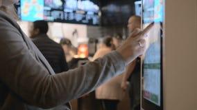 Donna che sceglie alimento tramite macchina di self service al fast food La gente facendo uso del terminale di tocco di self serv stock footage