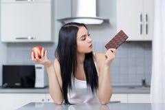 Donna che sceglie ciarpame o alimento sano, tenendo mela e cioccolato fotografia stock